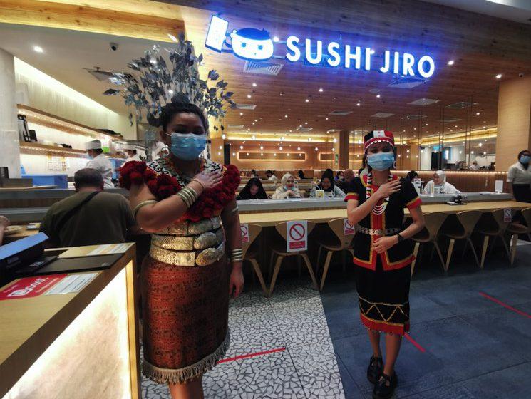 Gadis peraga pakaian tradisional Iban dan Bidayuh sambil hidang 'sushi' di pusat beli belah Viva